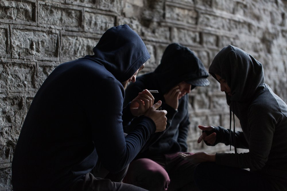 close up of young people smoking cigarettes and drugs
