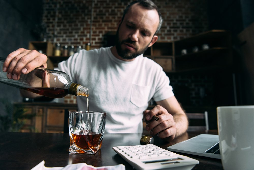 Depressed young man pouring whiskey in glass