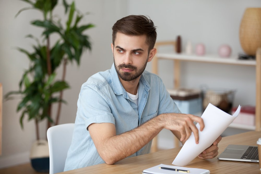 Serious thoughtful man looking away holding documents