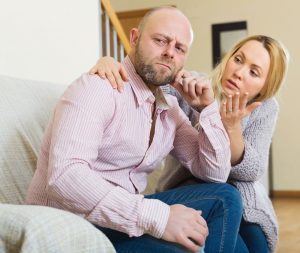 loving wife consoling husband on sofa at home