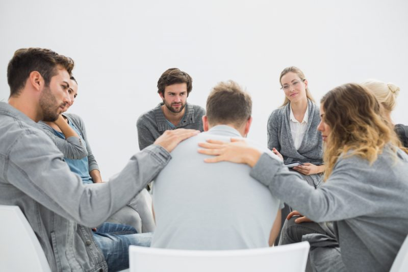 Group consoling a man during addiction and depression group therapy