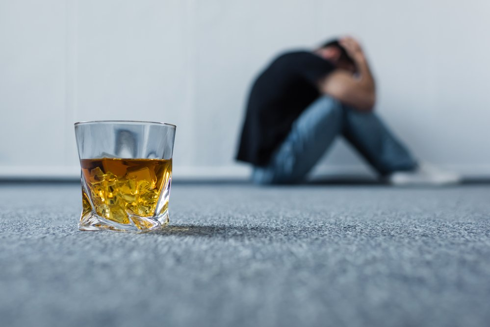 Glass of liquor and a man suffering in the background - what are the stages of alcoholism